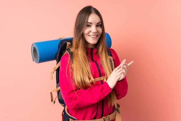 Jonge bergbeklimmervrouw met een grote rugzak die bij het roze muur toejuichen wordt geïsoleerd