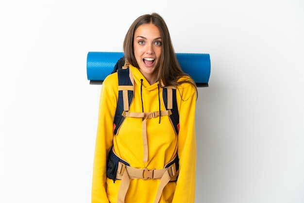 Jonge bergbeklimmervrouw met een grote rugzak die met verrassingsgelaatsuitdrukking wordt geïsoleerd