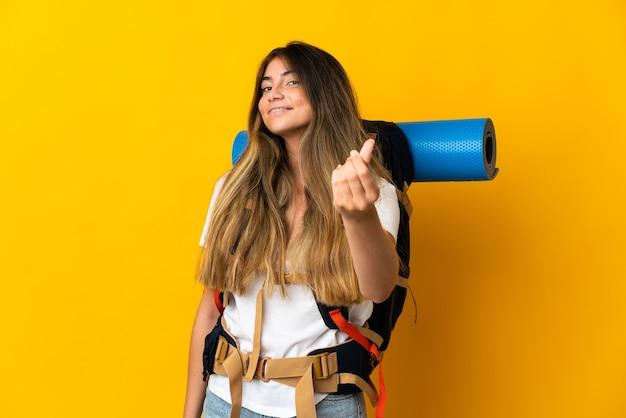 Jonge bergbeklimmervrouw met een grote rugzak die op gele muur wordt geïsoleerd die geldgebaar maakt