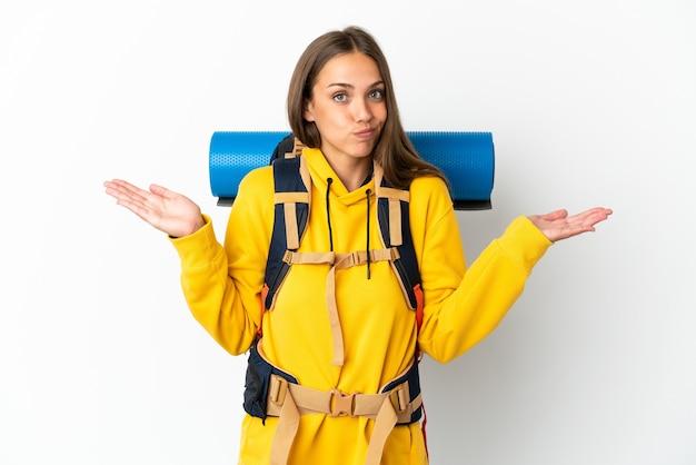 Jonge bergbeklimmervrouw met een grote rugzak geïsoleerd die twijfels heeft terwijl ze handen opsteekt