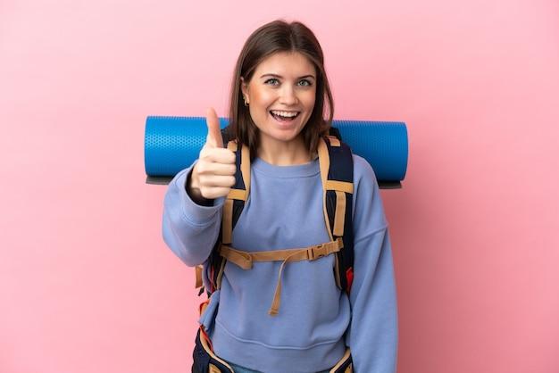 Jonge bergbeklimmervrouw met een grote rugzak geïsoleerd met duimen omhoog omdat er iets goeds is gebeurd