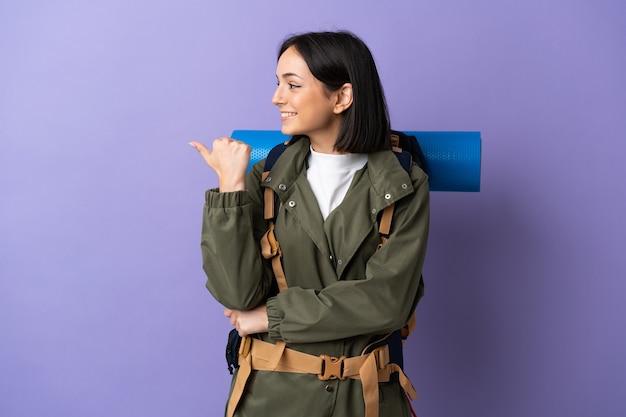 Jonge bergbeklimmervrouw met een grote rugzak over geïsoleerd die naar de kant wijst om een product te presenteren