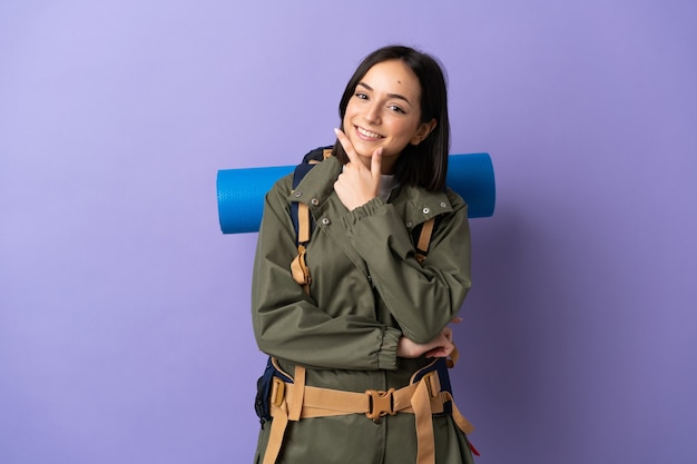 Jonge bergbeklimmervrouw met een grote rugzak over geïsoleerd gelukkig en glimlachend