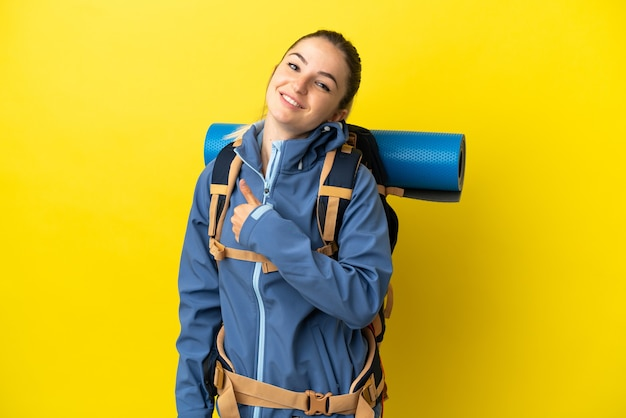 Jonge bergbeklimmervrouw met een grote rugzak over geïsoleerde gele achtergrond die een duim omhoog gebaar geeft