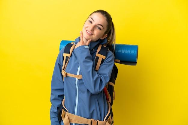 Jonge bergbeklimmervrouw met een grote rugzak over geïsoleerde gele achtergrond gelukkig en glimlachend