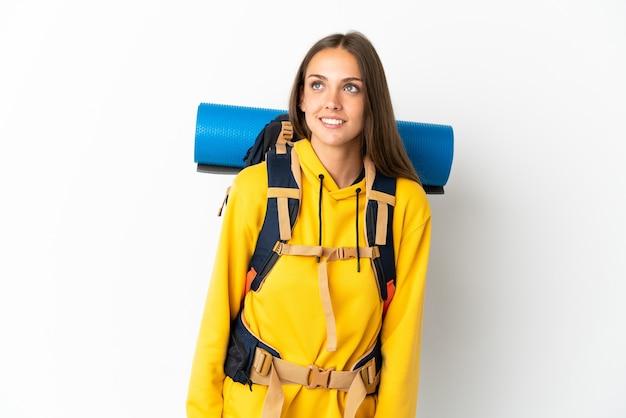 Jonge bergbeklimmervrouw met een grote rugzak over geïsoleerde witte achtergrond die een idee denken terwijl het kijken omhoog