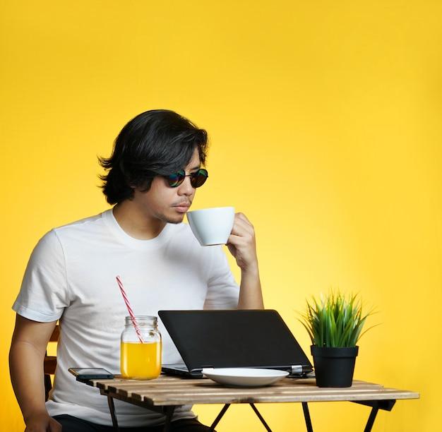 Jonge beroeps die van zijn koffie geniet terwijl het werken aan de zomervakantie tegen gele achtergrond