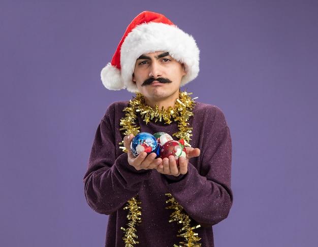 Jonge besnorde man met een kerstmuts met klatergoud om zijn nek en verwarde kerstballen die over een paarse muur staan