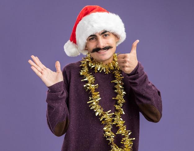 Jonge besnorde man met kerst-kerstmuts met klatergoud om zijn nek kijken naar camera met glimlach op gezicht presenteren met arm van de hand staande over paarse achtergrond