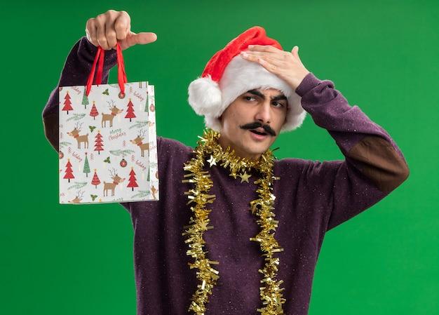 Jonge besnorde man met kerst-kerstmuts met klatergoud om zijn nek met papieren zak met kerstcadeau en kijkt verward met de hand op zijn hoofd voor een fout