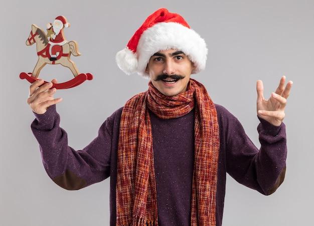 Jonge besnorde man met kerst kerstmuts met warme sjaal om zijn nek met kerst speelgoed kijken camera blij en opgewekt met opgeheven arm staande op witte achtergrond