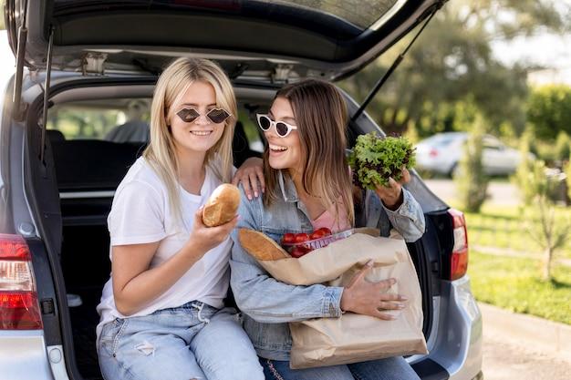 Jonge beste vrienden die in de kofferbak van een auto hangen