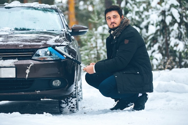 Jonge bestuurder een man reinigt de koplampen van een auto van sneeuw in de winter