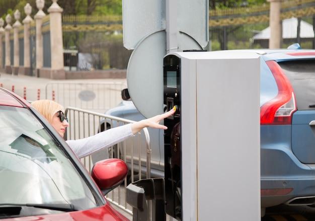 Jonge bestuurdersvrouw die een knoop op parkerenmachine drukken.