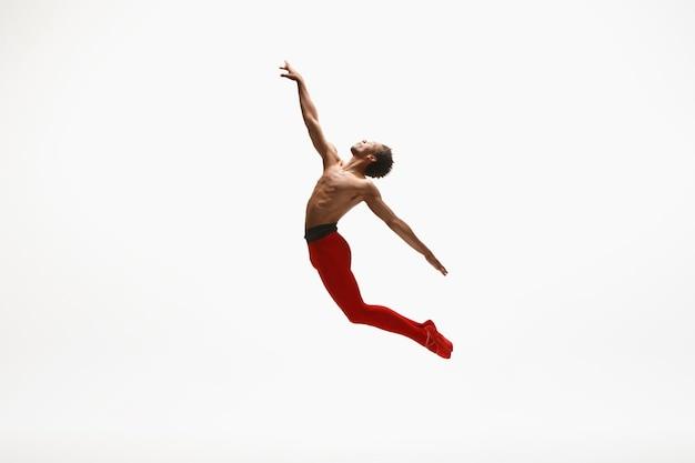 Jonge bevallige mannelijke balletdanser die op witte studioachtergrond danst