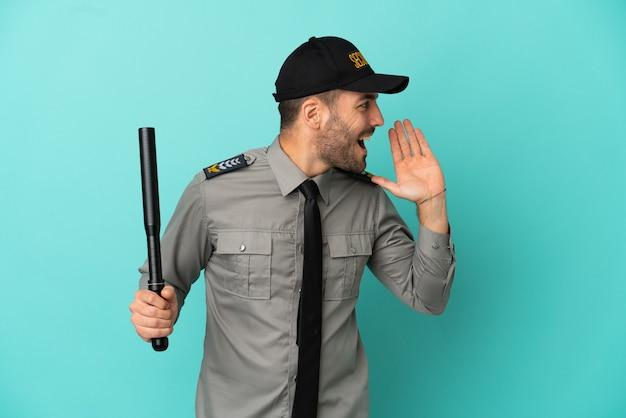 Jonge beveiligingsman geïsoleerd op blauwe achtergrond schreeuwend met mond wijd open naar de zijkant