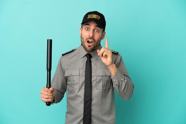 Jonge beveiligingsman geïsoleerd op een blauwe achtergrond die van plan is de oplossing te realiseren terwijl hij een vinger opheft