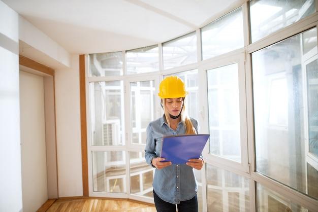 Jonge bezorgd vrouwelijke ingenieur met een gele helm op haar hoofd te kijken naar haar blauwdruk.