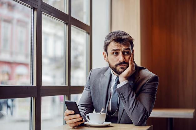 Jonge bezorgd zakenman zitten in coffeeshop, slimme telefoon te houden en na te denken over baan.