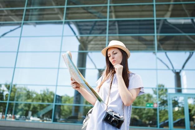 Jonge bezorgde reiziger toeristische vrouw met retro vintage fotocamera op zoek in papieren kaart, zoek route op internationale luchthaven