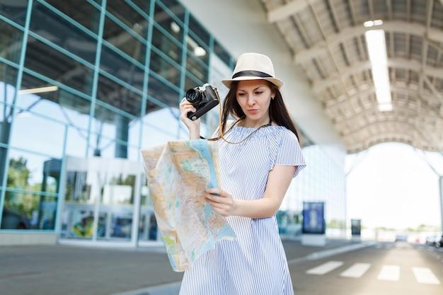 Jonge bezorgde reizigerstoeristenvrouw in hoed houdt retro vintage fotocamera vast, kijkend naar papieren kaart op internationale luchthaven