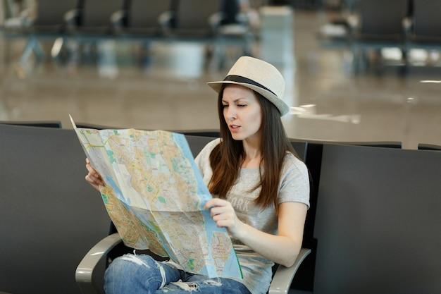 Jonge bezorgde reizigerstoeristenvrouw met papieren kaart, route zoeken, wachten in de lobby op de internationale luchthaven