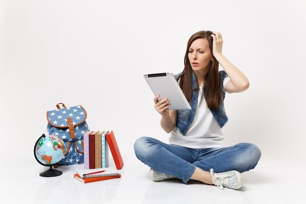 Jonge bezorgde studente die een tablet-pc-computer gebruikt en de hand op het hoofd houdt terwijl ze in de buurt van de wereld zit, rugzak schoolboeken geïsoleerd