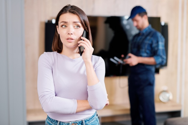 Jonge bezorgde vrouw die haar vriend belt om over gebroken plasmapaneel te raadplegen met reparateur
