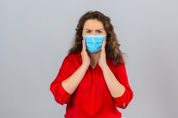 Jonge bezorgde vrouw die rode blouse in medisch beschermend masker draagt ?? wat betreft wangen die aan kiespijn lijden over geïsoleerde witte achtergrond