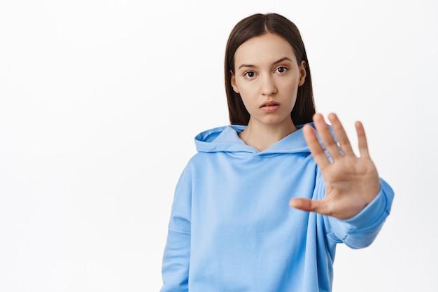 Jonge bezorgde vrouw steekt hand uit en zegt nee, oneens, verbied of verwerp iets, taboe-gebaar, staande in hoodie tegen witte muur.