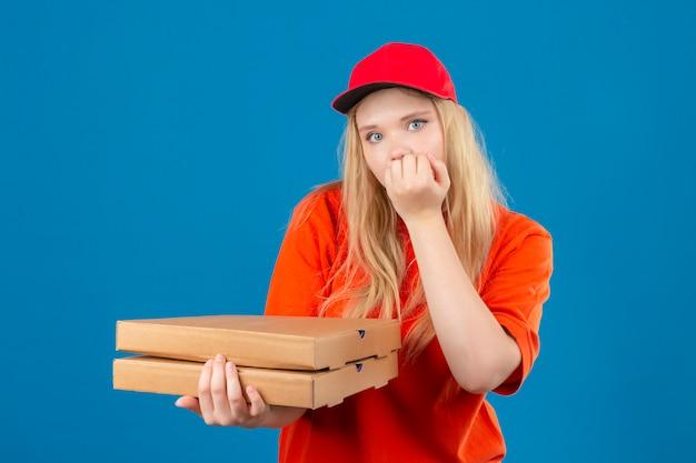 Jonge bezorger die een oranje poloshirt en een rode pet draagt en een stapel pizzadozen vasthoudt die gestrest en nerveus kijken met de handen op de mond nagels bijten over geïsoleerde blauwe achtergrond