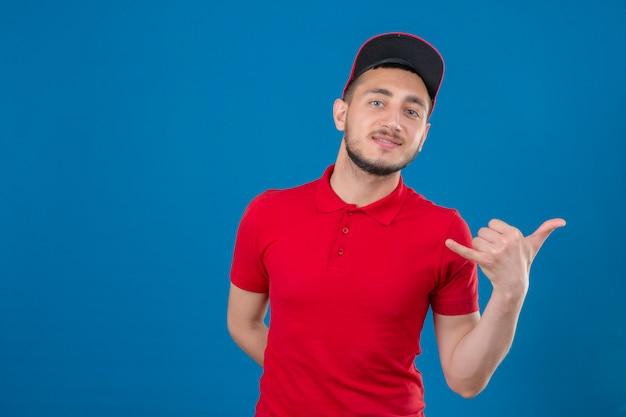 Jonge bezorger die een rood poloshirt en een pet draagt en bel me gebaar maakt op zoek naar zelfverzekerd over geïsoleerde blauwe achtergrond