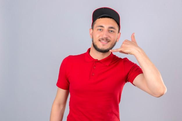Jonge bezorger die een rood poloshirt en een pet draagt en bel me gebaar maakt op zoek naar zelfverzekerd over geïsoleerde witte achtergrond
