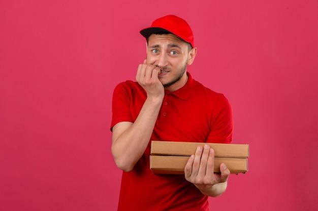 Jonge bezorger die een rood poloshirt en een pet met pizzadozen draagt die er gestrest en nerveus uitziet met de handen op de mond nagels bijten over geïsoleerde roze achtergrond