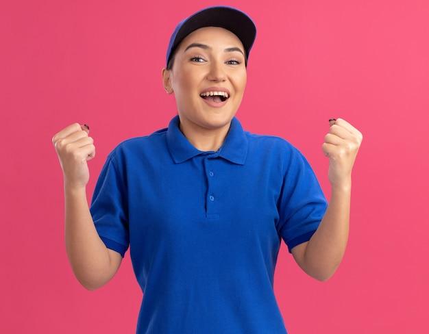 Jonge bezorger die in blauw uniform en pet naar voren kijkt, gebalde vuisten blij en opgewonden staande over roze muur