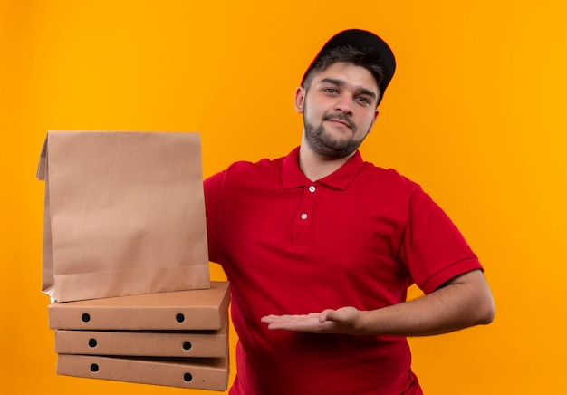 Jonge bezorger die in rood uniform en glb document pakket en stapel pizzadozen voorstelt die er zelfverzekerd uitzien