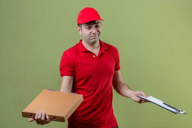Jonge bezorger die rode uniform draagt met kartonnen dozen en klembord met twijfels met verwarren gezichtsuitdrukking over geïsoleerde groene achtergrond