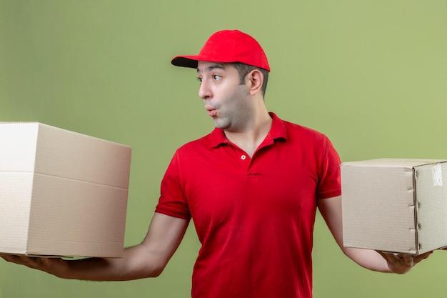 Jonge bezorger die rode uniforme kartonnen dozen draagt die zich over geïsoleerde groene achtergrond bevinden verbaasd kijken
