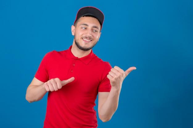 Jonge bezorger die rood poloshirt en pet draagt ?? die met een blij gezicht glimlacht en naar de kant kijkt met duimen omhoog over geïsoleerde blauwe achtergrond
