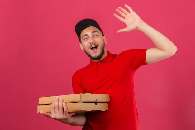 Jonge bezorger die rood poloshirt en pet draagt die met hand met gelukkige uitdrukking over geïsoleerde roze achtergrond groeten