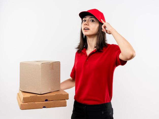 Jonge bezorger die rood uniform en pet draagt met doos pakket en pizzadozen die met wijsvinger naar haar tempel wijzen en zelfverzekerd kijken gericht op een taak die over een witte muur staat