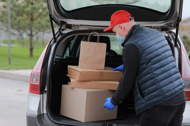 Jonge bezorger in beschermend masker, rode pet en handschoenen in de buurt van de auto met dozen en pakketten, buitenshuis