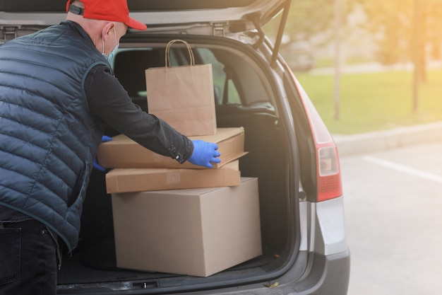 Jonge bezorger in beschermend masker, rode pet en handschoenen in de buurt van de auto met dozen en pakketten