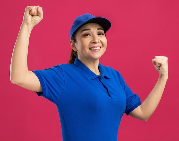 Jonge bezorger in blauw uniform en pet blij en opgewonden met gebalde vuisten over roze muur