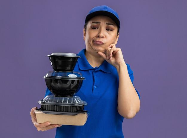 Jonge bezorger in blauw uniform en pet die een stapel voedselpakketten vasthoudt en ze verward aankijkt terwijl ze over een paarse muur staan