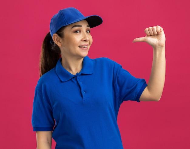 Jonge bezorger in blauw uniform en pet die zelfverzekerd glimlacht