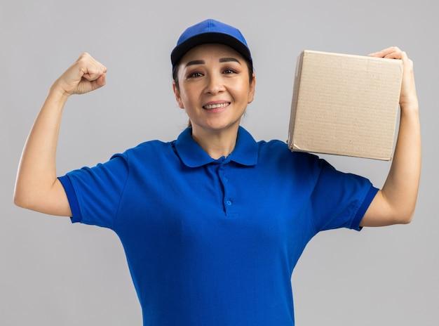 Jonge bezorger in blauw uniform en pet met kartonnen doos blij en opgewonden die vuist opheft die vrolijk over witte muur staat