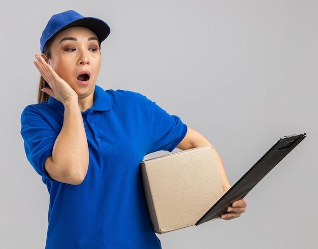 Jonge bezorger in blauw uniform en pet met kartonnen doos en klembord die er verbaasd en verrast uitziet
