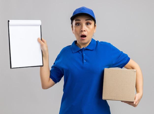 Jonge bezorger in blauw uniform en pet met kartonnen doos met klembord verbaasd en verrast