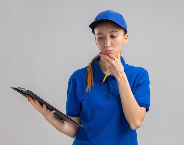 Jonge bezorger in blauw uniform en pet met klembord die ernaar kijkt met een peinzende uitdrukking die over een witte muur staat te denken